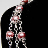 Photo of cranberry red glass pearl necklace with elegant/frilly holiday enhancements on shiny metal chain.