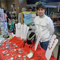 Photo of Marie Gilvey standing behind her display as shoppers take advantage of her special deal on free jewelry.