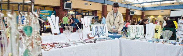 Marie Gilvey prepares a new bead necklace while customers enter the craft show.