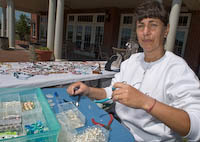 Marie Gilvey makes another necklace during the Port Potomac Vendor Fair