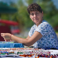 Marie Gilvey makes a new bead necklace design during a light moment.